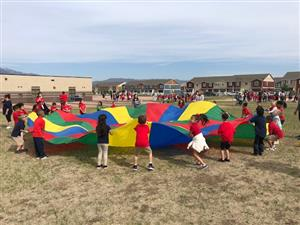 Students playing with large parachute.